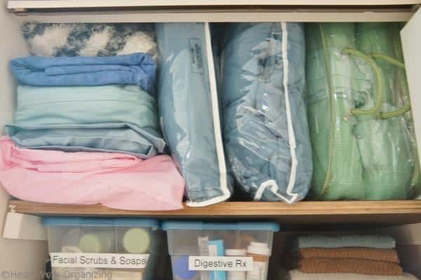 extra bed linens organized in  bathroom linen closet