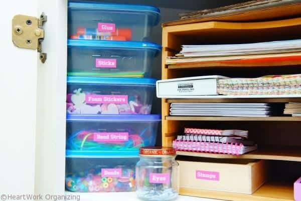 use plastic tubs to organize craft cabinet
